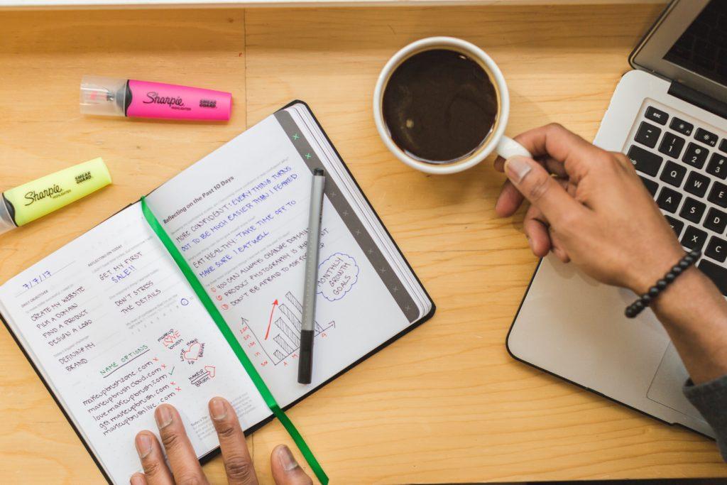 Tách cà phê và sổ tay trên bàn làm việc màu vàng