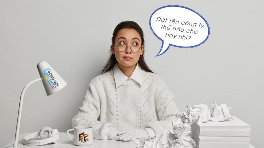 cô gái đeo kính mặc áo trắng nhìn sang bên trái cạnh chiếc đèn bàn, cái cốc và xấp giấy khi start up đặt tên công ty nguyễn thị mỹ ngọc